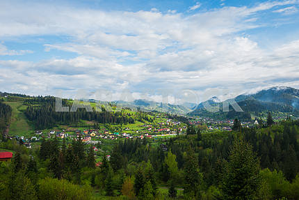 spring in the Carpathian mountains, Ukraine, sunny morning, view from high above, a little city and forrest hills on the landscape, blue sky and white clouds, a little fog on the top of the hill