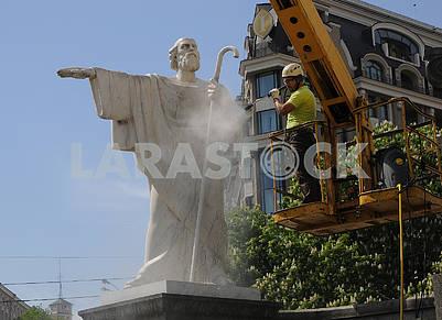 Работник клининговой компании моет памятник Андрею Первозванному