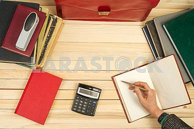 On a wooden table books, documents, calculator, red briefcase.