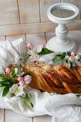 Tasty braided buns on lacy napkin and shabby background