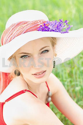 Portrait of a beautiful young girl in a white hat