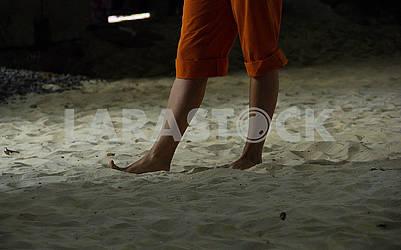 Girl goes on the sand. Bare feet.