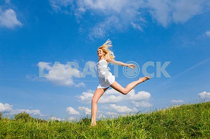 Happy woman is running on a field