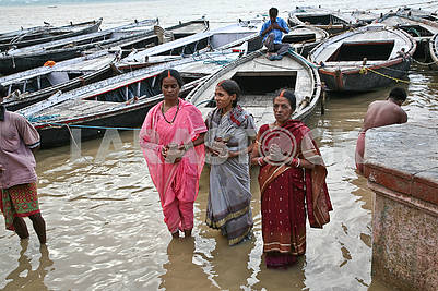 11Three Indian women are washed in the waters of the sacred rive