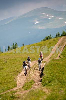 Tourists with backpacks on the bike in the Carpathian Mountains