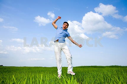 Happy man is jumping in a field