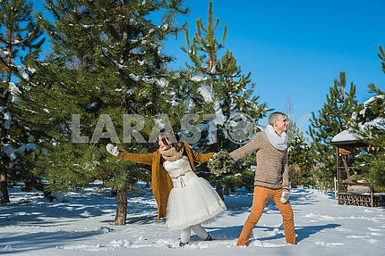 Wedding couple in a showy wither day, walking, having fun behind the pine-tree. rustic style  short wedding dress. Girl brunette. beautiful bride