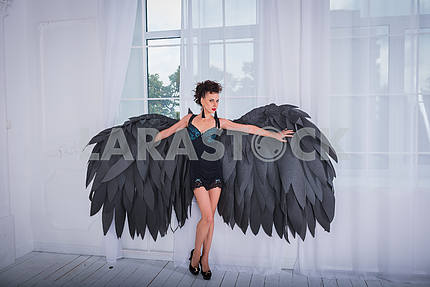 Brunette woman - black angel with the big wings, red lips, black short suit, in white room  standing near the window