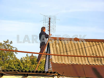 A man repairs an antenna on a house roof