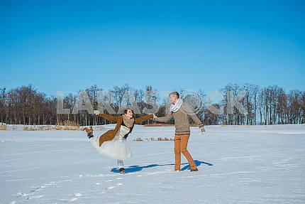Молодая пара свадьба, играя в снегу в Солнечный зимний день. Свадьба в деревенском стиле. Милая девушка в коротком свадебном белом платье, голубое небо на заднем плане. Браун свадьба стиль. Танцы