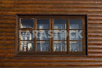 Wooden window of a wooden house decorated bottles