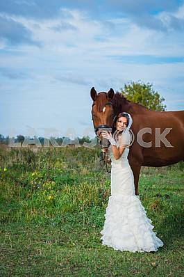 Brown-haired woman standing in front of a horse, in wedding dress mermaid silhouette, blue sky on the background