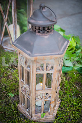Vintage wooden lantern with the candle and moss on the background wedding decorations