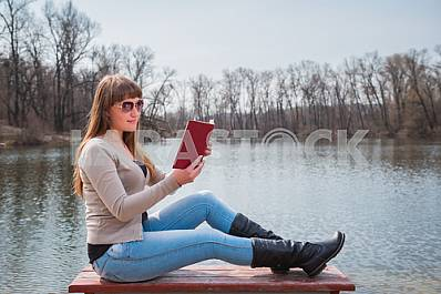 Young woman reading the book outdoor in sunglasses, daily lifestyle, river on the background, spring, sunny day