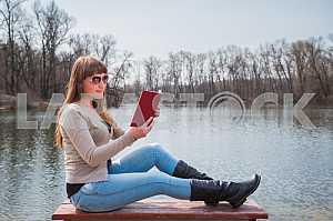 Молодая женщина читает книгу на открытом воздухе в солнечных очках, ежедневный образ жизни, река на заднем плане, весенний, солнечный день
