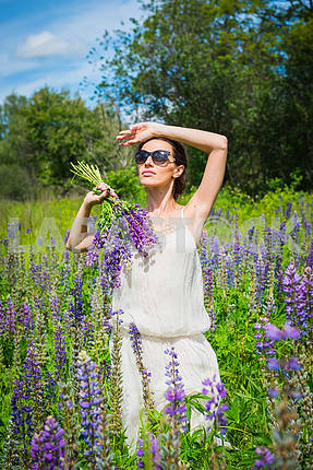 Young woman, happy, standing among the field of violet lupines, smiling, purple flowers. Blue sky on the background. Summer, with bouquet, in sunglasses holding her hand near head