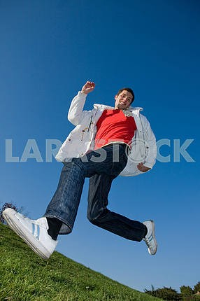 Happy young man - jumping in blue sky