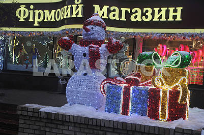 Snowman and boxes with gifts near the store
