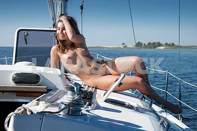 Naked girl resting on deck