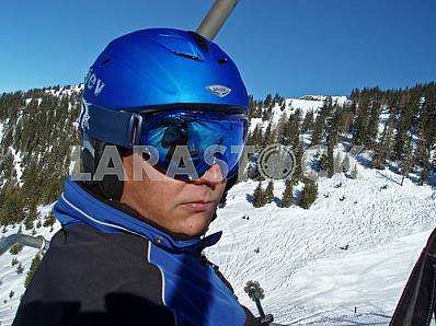 A skier in helmet and goggles. The ski slopes of the