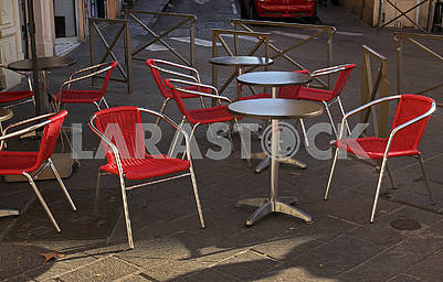 Gray round tables and red chairs in a cafe