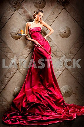 Beautiful girl in long red dress holds exotic flower in hand