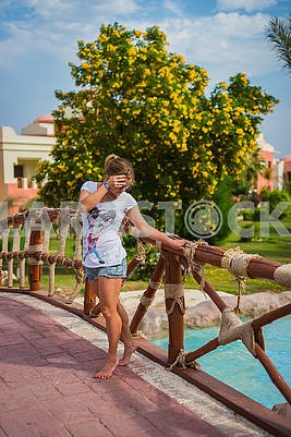 A young woman standing on the bridge near the pool. having rest in Egypt . green tree with the yellow  flowers on the background. travel