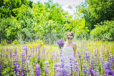 Young woman, happy, standing among the field of violet lupines, smiling, purple flowers. Blue sky on the background. Summer, sunny day! with bouquet