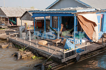 On the terrace of the house of the village on the water Tonle Sap Lake in Cambodia in a hammock relaxing family