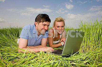 Casual happy couple on laptop computer outdoors. Lay on the gree