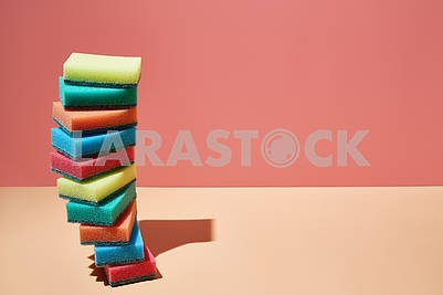 A stack of multi-colored sponges for dishes on a bright 3D background with childish sunlight and shadow. copyspace