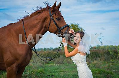Portrait of brown-haired woman standing in front of a horse, in wedding dress mermaid silhouette, blue sky on the background