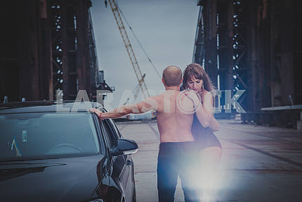 Beautiful blonde girl standing sexy on the unfinished bridge, with the men topless back and car, in black corset on a windy day, grey clouds, holding each other
