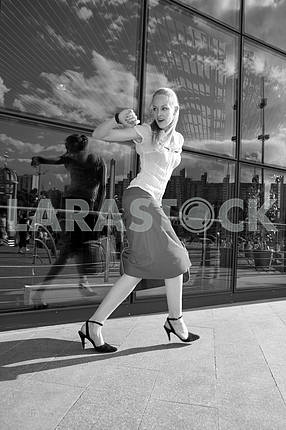 Black and White Young woman, blond, runs against the backdrop of