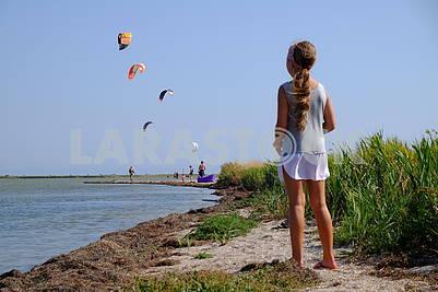 The girl watches kitesurfing
