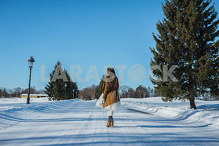 Walking bride on a snowy road. beautiful brunette in a short wedding dress, rustic style, with the pine-tree wedding bouquet, and in brown boots and knitted sweater, sunny blue sky on the background