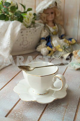 Elegant antique white tea cup on shabby table, vertical image