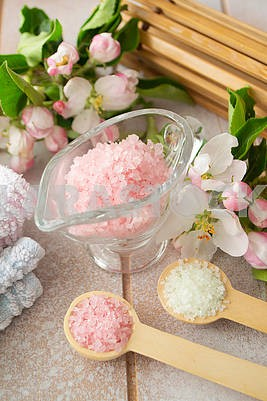 Spa or wellness setting. Pink sea salt, towels and apple blossom on shabby wooden background.