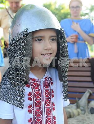 A boy in a knight's helmet