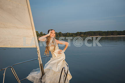 Wedding on a yacht. Beauty bride. Beautiful model girl in white/creamy dress. Female  portrait. Woman posing. Cute lady outdoors. Kyiv sea resrvoir.  wooden yacht evening sun
