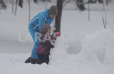 Girl sculpts snowman