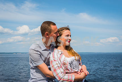 A couple in love - embracing, together, holding with the hands, near the water on a sunny day, blue sky with long white clouds on the background. men and women are looking into their future, smiling.
