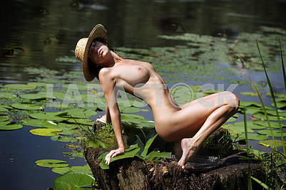 Naked girl in a straw hat