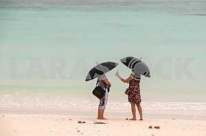 Tourists on the beach of Zanzibar during a rain.