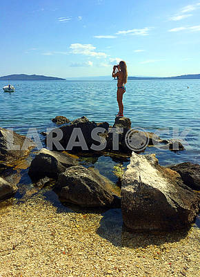Slim girl with a camera on the stone