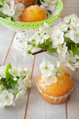 Golden muffin cupcakes, vertical image, spring flowers on shabby table