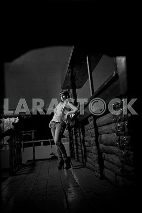 Black and white photo, far away a woman standing in a bar in jeans, waiting, dark, wooden room