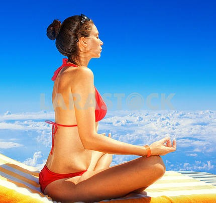 Young woman sitting in lotus position on a background of blue sk