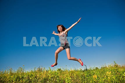 Happy young woman jumping in a field