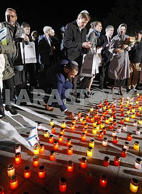 People light candles and lay flowers